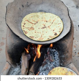 Indian traditional stove or oven. Wood burning under the clay pan. Baking Indian bread or chapatti. Corn flour bread. Tasty Indian rural food.