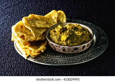 Indian traditional tasty palak paneer with tandori butter naan on the ornament plate with rich spoon. Indian cuisine: palak paneer , food Spinach and Indian cottage cheese curry. Dark foodphoto