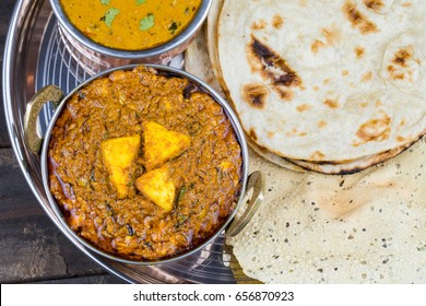 Indian Traditional Thali Food Kadai Paneer Served With Dal Makhani, Tandoori Roti or Papad on Vintage Wooden Background