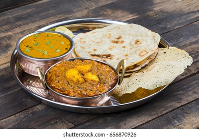 Indian Traditional Thali Food Kadai Paneer Served With Dal Makhani, Tandoori Roti or Papad on Vintage Wooden Background