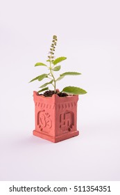 Indian traditional tulsi pot or special masonry structure known as Tulsi Vrindavan or Tulsi vrundavan with swastik and aum writting, holy hindu object, isolated, selective focus