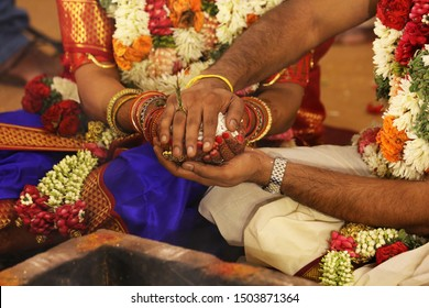 Indian traditional wedding bride and grooms hands together ritual ceremony