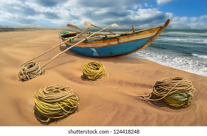 Indian traditional wooden fishing boat on the coastline ocean and marine rope in the foreground. Orissa, India
