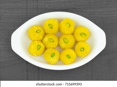 Indian Traditional Yellow Sweet Food Coconut Laddoo Also Know As Coconut Laddu, Ladoo, laddo Are Ball-Shaped Sweets. Dark Wooden Background