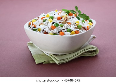 indian veg biryani, veg pulav, Indian vegetable pulav, Biriyani, vegetable Biriyani served in a ceramic bowl on reddish brown background