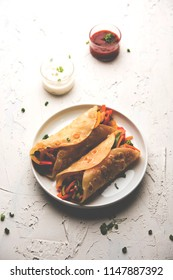 Indian Veg chapati Wrap / Kathi Roll, served in a plate with sauce over moody background. selective focus