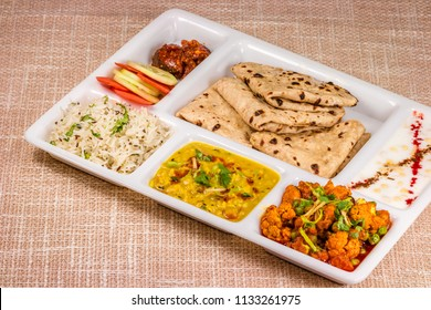 Indian Veg Thali consists of a big platter in which their are little bowl of variety of veggies, lentils, sweet dish, snacks etc. It also included pickles. A popular daily indian food.