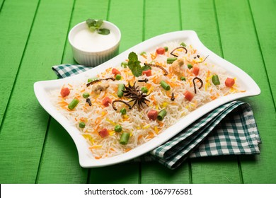 Indian Vegetable Pulav or Biryani made using Basmati Rice, served in white ceramic plate. selective focus
