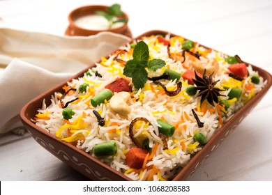 Indian Vegetable Pulav or Biryani made using Basmati Rice, served in a terracotta bowl. selective focus