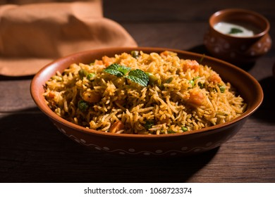 Indian Vegetable Pulav or Biryani made using Basmati Rice, served in terracotta bowl. selective focus