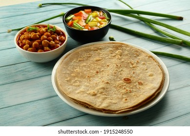 Indian vegetarian food - homemade fresh  chapati served with vegetable stew and chickpeas curry on a rustic background.
