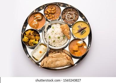 Indian vegetarian Food Thali or platter includes paneer butter masala, dal makhani / tarka, chole papad, kofta curry, gulab jamun, aloo-gobi sabji, chapati and rice with Bengali sweet served