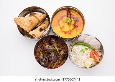 Indian vegetarian Lunch Box or Tiffin made up of stainless steel for office or workplace, includes Dal Fry, Baingan Masala, Rice with chapati and salad