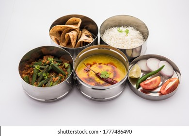 Indian vegetarian Lunch Box or Tiffin made up of stainless steel for office or workplace, includes Dal Fry, Bhindi Masala, Rice with chapati and salad