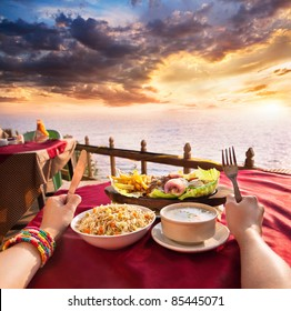 Indian vegetarian sizzler, corn soup and fried rice on the table at ocean and dramatic sunset background. Hands with fork and knife on the table