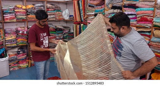 indian village garment store shopkeeper showing women sari to the male customer in the showroom at district Katni Madhya Pradesh in India shot captured on sep 2019