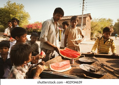 Indian village street shopkeeper selling watermelon to children on 2 may 2016, Lalitpur, India.