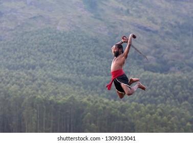 Indian warrior fighter jumping up. Kalaripayattu Marital art demonstration in Kerala, South India
