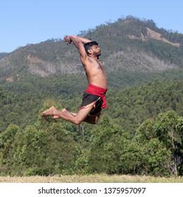 Indian warrior jumping up during Kalaripayattu Marital art demonstration in Kerala, South India