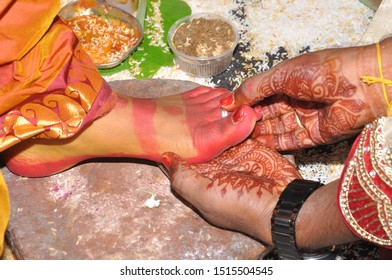 Indian Wedding for bride groom is keeping the toe ring to bride's foot. it is the culture of marriage in india.