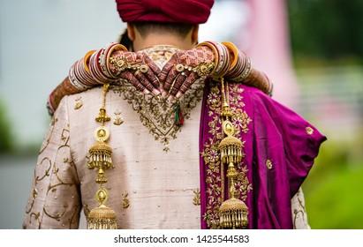 Indian wedding couple hugging and bridal showing mehndi design