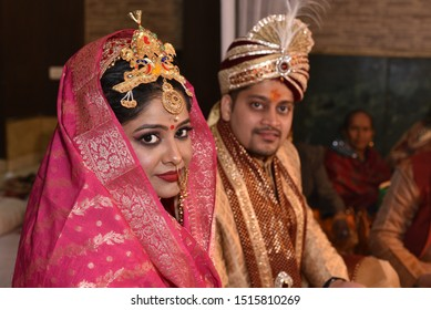 Indian wedding couple posing for photograph. Beautiful bridal makeup of bride is visible with groom in bokeh effect