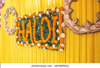 Indian wedding decoration with Haldi (Meaning - turmeric) . written text using yellow marigold flowers on green leaves placed on beautiful vibrant curtain. Selective focus on floral decor, background.