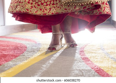 Indian Wedding. Female foot with high heels, Beautiful National Indian Bridal Mehendi in Legs. Eastern Traditional Lehnga clothes.