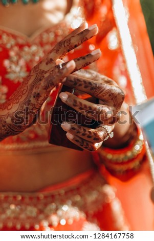 4fea9debe3343 Indian wedding. First look. Hindu bride in red lehega holds box with  traditional wedding rings in her arms with henna tattoo - Image