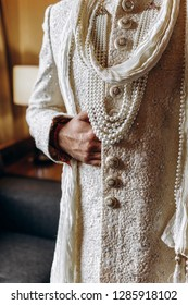 Indian wedding. Groom's preparetions. Hindu groom in rich white wedding sherwani stands in a hotel room