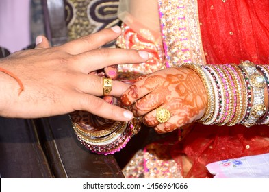 Indian wedding hands holding bride and grooms. Indian culture marriage bride hand with beautiful red bangle. ring ceremony before marriage.