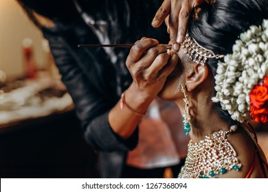 Indian wedding. Morning preparetions. Adorable Hindu bride in traditional red lehenga with gold sits straight and calm while artist does her make-up