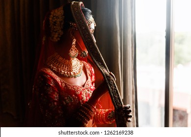 Indian wedding. Morning preparetions. Portrait of attractive Hindu bride with rich jewelry and deep dark eyes
