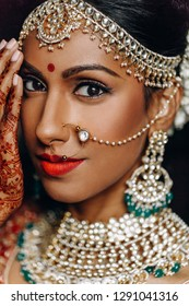 Indian wedding. Morning preparetions. Portrait of attractive Hindu bride with rich jewelry and deep dark eyes, holding palms on her face
