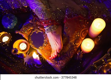 Indian Wedding Preparation. Luxury Oriental Fashion Accessories: Female foot, Beautiful National Indian Bridal Golden Jewellery. Eastern Traditional Sari clothes. Color lenses, Candlelight, soft focus