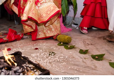 Indian wedding rituals. Bengali bride removing betel leaf and betel nuts by her feet using a stone.