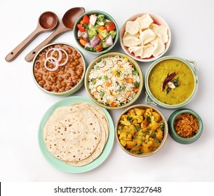 Indian whole vegetarian meal with yellow dal, vegetable pulao, chapati,gulab jamun, salad, papad, pickle, chana masala curry and aloo gobi