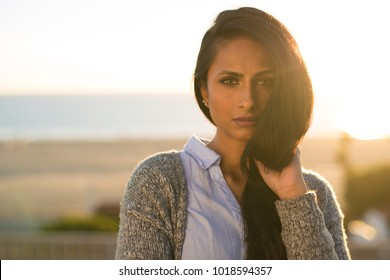 Indian woman backlit sunset serious face portrait