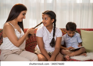Indian woman braiding hair of her teenage daughter