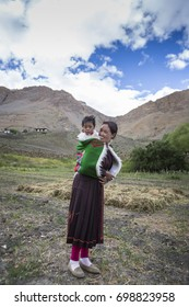 indian woman carrying baby on her back in spiti valley, India