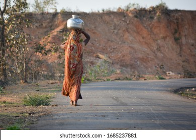 An Indian woman carrying a container of water on her head
