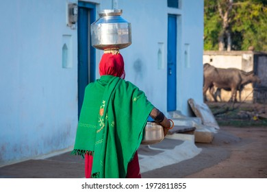 An Indian woman carrying a container of water on her head, An Indian rural scene.