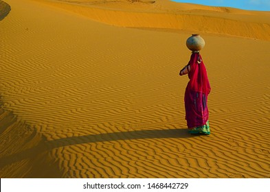 Indian woman carrying heavy jug of water on her head and walking on a yellow sand dune in the hot summer desert against blue sky.water crises, jaisalmer, rajasthan, india