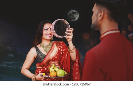 Indian woman celebrating Karva Chauth by looking at her husband after looking at the moon at night
