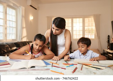 Indian woman checking how her children doing homework