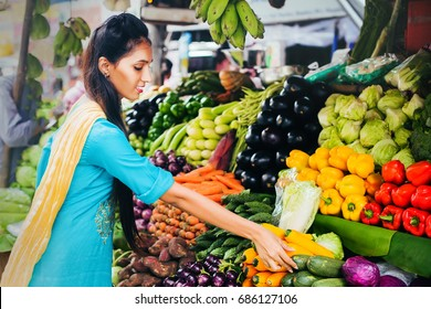 indian woman choosing vegetables on a market