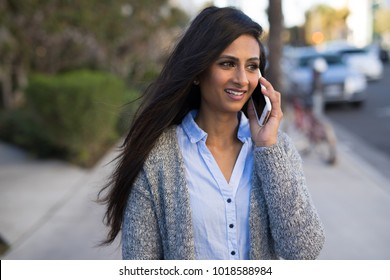 Indian woman in city walking street talking on cell phone