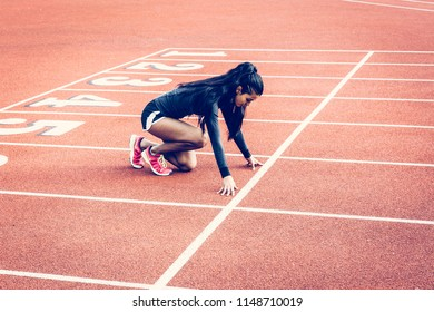 Indian woman crouched in starting position on a running track. Multicultural, ethnic and inclusive theme.