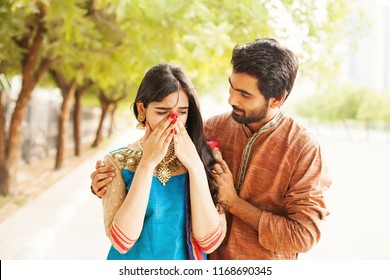 Indian woman crying and man comforting her