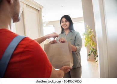 Indian woman customer taking delivery paper eco bag with grocery takeout food meal from man courier holding paper package delivering supermarket or restaurant takeaway order standing at door at home.